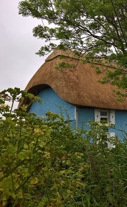 Blue cottage with a thatched roof, Ireland.