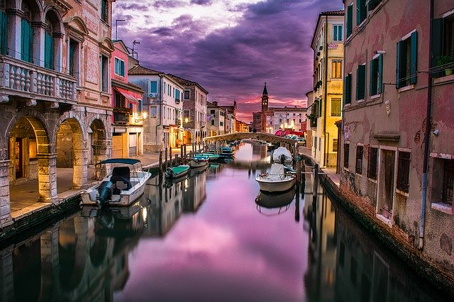 Venice - Moody image of canal, boats, buildings and sky.