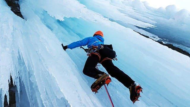 Ice Climber scaling the ice - Extreme Sports