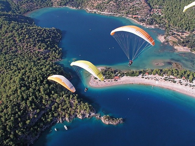 Parachuting over blue water - Extreme Sports