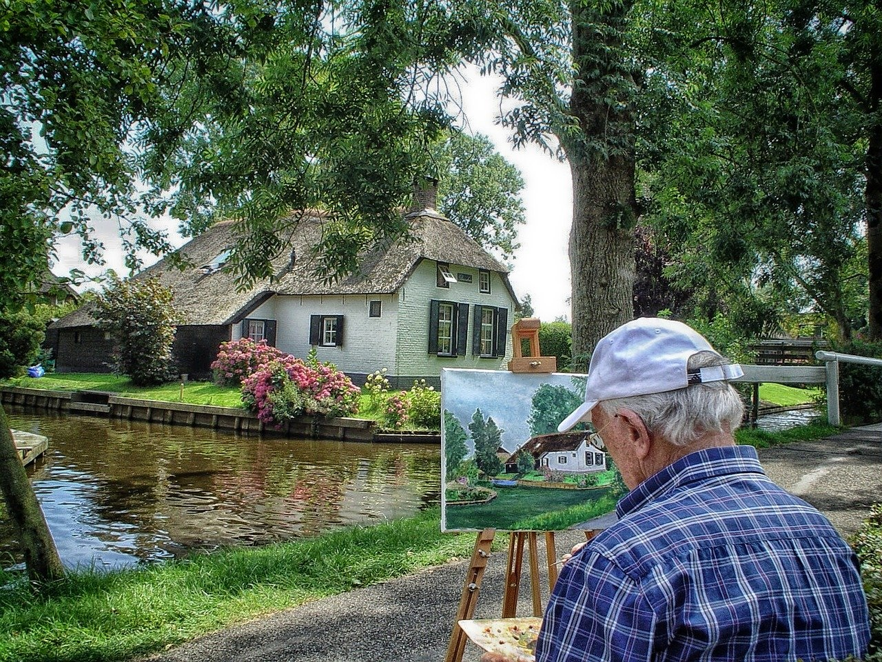 Artist Painting a Thatched Roof Cottage in Netherlands