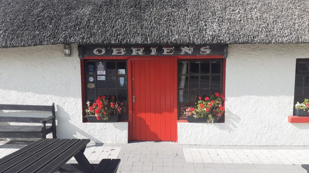 Traditional Thatched Roof Pub with White painted Walls and a Red Door