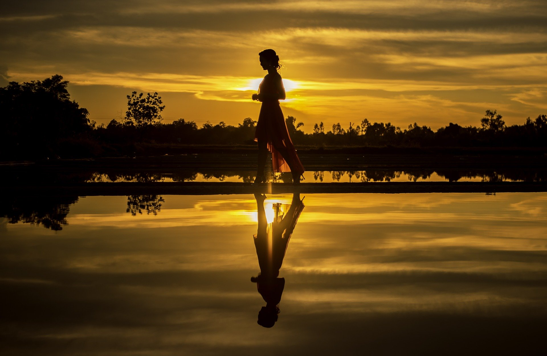 Woman walking near water at sunset